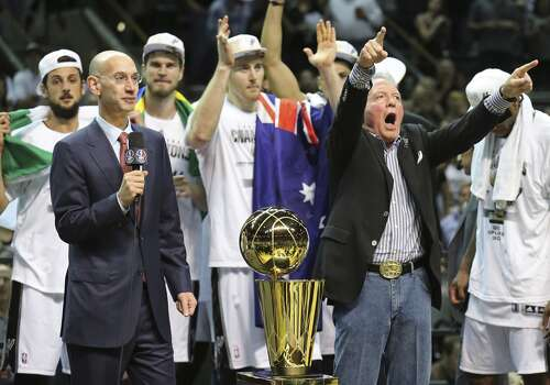 National Basketball Association commissioner Adam Silver (left) speaks after Game 5 of the 2014 NBA Finals as San Antonio Spurs owner Peter Holt and the team celebrate after defeating the Miami Heat Sunday June 15, 2014 at the AT&T Center. The Spurs won 104-87. Photo: San Antonio Express-News
