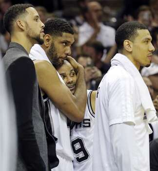 San Antonio Spurs' Tim Duncan hugs Tony Parker between Austin Daye and Danny Green on the bench late in Game 5 of the 2014 NBA Finals against the Miami Heat Sunday June 15, 2014 at the AT&T Center. The Spurs won 104-87. Photo: San Antonio Express-News