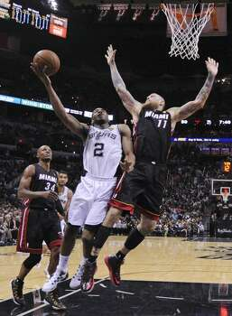 San Antonio Spurs' Kawhi Leonard shoots between Miami Heat's Ray Allen and Chris Andersen in Game 5 of the 2014 NBA Finals Sunday June 15, 2014 at the AT&T Center. The Spurs won 104-87. Photo: San Antonio Express-News