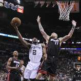 San Antonio Spurs' Kawhi Leonard shoots between Miami Heat's Ray Allen and Chris Andersen in Game 5 of the 2014 NBA Finals Sunday June 15, 2014 at the AT&T Center. The Spurs won 104-87.