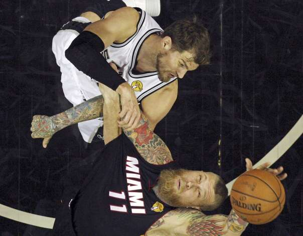 San Antonio Spurs' Tiago Splitter and Miami Heat's Chris Andersen grab for a rebound in Game 5 of the 2014 NBA Finals Sunday June 15, 2014 at the AT&T Center. The Spurs won 104-87. Photo: San Antonio Express-News