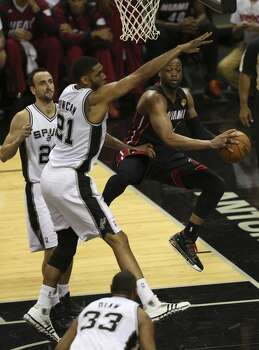 Miami Heat's Dwyane Wade passes out to the perimeter as San Antonio Spurs' Tim Duncan and Manu Ginobili defend during the first quarter of game five of the NBA Finals at the AT&T Center, Sunday, June 15, 2014. Photo: San Antonio Express-News