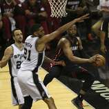 Miami Heat's Dwyane Wade passes out to the perimeter as San Antonio Spurs' Tim Duncan and Manu Ginobili defend during the first quarter of game five of the NBA Finals at the AT&T Center, Sunday, June 15, 2014.