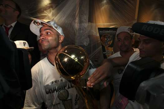 San Antonio Spurs' Tony Parker holds the Larry O'Brien NBA Championship trophy after defeating the Miami Heat at the AT&T Center, Sunday, June 15, 2014. Photo: San Antonio Express-News