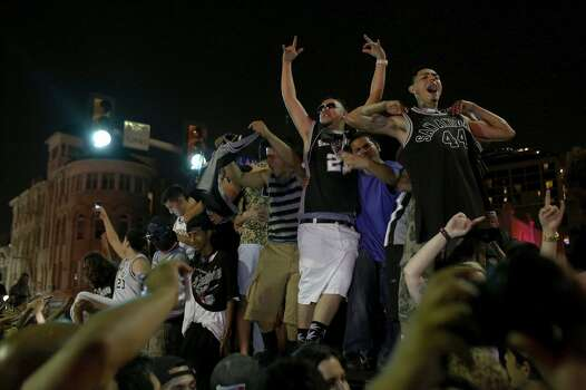 Fans celebrate the Spurs winning the NBA Championship after beating the Miami Heat as they stand on top of a car on Commerce Street in downtown San Antonio on Sunday, June 15, 2014 Photo: SAN ANTONIO EXPRESS-NEWS