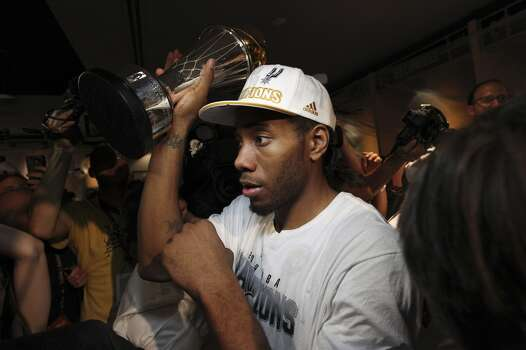 San Antonio Spurs' Kawhi Leonard carries the Larry O'Brien NBA Championship trophy inside the team's locker room after defeating the Miami Heat at AT&T Center, Sunday, June 15, 2014. Photo: San Antonio Express-News