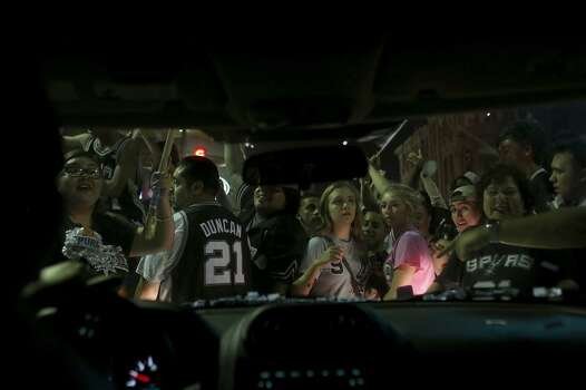 Driver Kelsey Mahan tries to inch her way through the crowd after getting stuck on Commerce Street as fans celebrate the Spurs winning the NBA Championship after beating the Miami Heat in downtown San Antonio on Sunday, June 15, 2014. Photo: SAN ANTONIO EXPRESS-NEWS