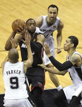 San Antonio Spurs' Tony Parker, Manu Ginobili and Danny Green surround Miami Heat's Dwyane Wade during game five of the NBA Finals at the AT&T Center, Sunday, June 15, 2014. Photo: San Antonio Express-News