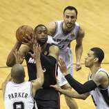 San Antonio Spurs' Tony Parker, Manu Ginobili and Danny Green surround Miami Heat's Dwyane Wade during game five of the NBA Finals at the AT&T Center, Sunday, June 15, 2014.