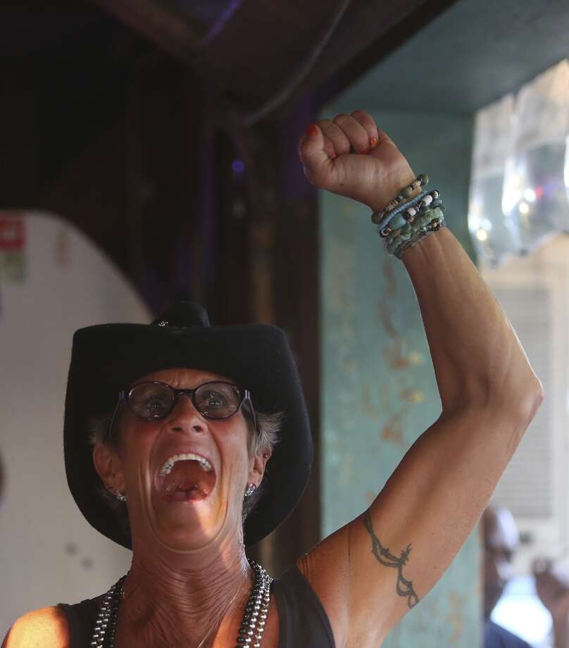 Tina Sutter cheers for the Spurs as she watches the game at Texas Ice Service, an icehouse on Blanco Road, as the Spurs play the Miami Heat during Game 5 of the NBA Finals in San Antonio on Sunday, June 15, 2014. Photo: SAN ANTONIO EXPRESS-NEWS