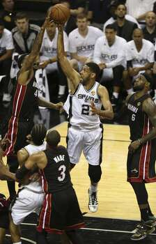 San Antonio Spurs' Tim Duncan shoots over Miami Heat's Udonis Haslem as LeBron James look on during the first quarter of game five of the NBA Finals at the AT&T Center, Sunday, June 15, 2014. Photo: San Antonio Express-News