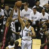 San Antonio Spurs' Tim Duncan shoots over Miami Heat's Udonis Haslem as LeBron James look on during the first quarter of game five of the NBA Finals at the AT&T Center, Sunday, June 15, 2014.