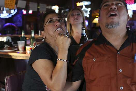 Leticia Garza, left, agonizes over a play with her boyfriend, Robert Lopez, at Texas Ice Service, an icehouse on Blanco Road, as they watch the Spurs play the Miami Heat during Game 5 of the NBA Finals in San Antonio on Sunday, June 15, 2014. Photo: SAN ANTONIO EXPRESS-NEWS