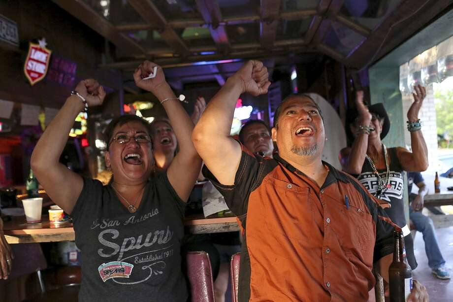 Leticia Garza, left, and her boyfriend, Robert Lopez, cheer for the Spurs at Texas Ice Service, an icehouse on Blanco Road, as they watch the Spurs play the Miami Heat during Game 5 of the NBA Finals in San Antonio on Sunday, June 15, 2014. Photo: SAN ANTONIO EXPRESS-NEWS