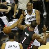 San Antonio Spurs' Boris Diaw passes to Tim Duncan as Miami Heat's Chris Bosh defends during the first quarter of game five of the NBA Finals at the AT&T Center, Sunday, June 15, 2014.