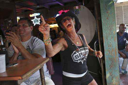 Tina Sutter shows her Spurs spirit as she watches the game with friends including Jay Sanchez, left, at Texas Ice Service, an icehouse on Blanco Road, as the Spurs play the Miami Heat during Game 5 of the NBA Finals in San Antonio on Sunday, June 15, 2014. Photo: SAN ANTONIO EXPRESS-NEWS