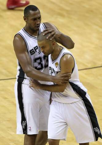 San Antonio Spurs' Boris Diaw hugs Tony Parker late in the fourth quarter of game five of the NBA Finals against the Miami Heat at the AT&T Center, Sunday, June 15, 2014. Photo: San Antonio Express-News