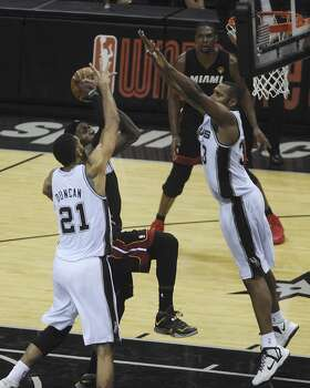 San Antonio Spurs' Tim Duncan, left, and Boris Diaw, right, collapse on LeBron James of the Miami Heat during first-half action in game 5 of the NBA Finals in the AT&T Center on Sunday, June 15, 2014. Photo: San Antonio Express-News