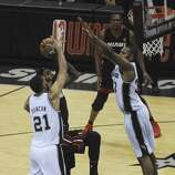 San Antonio Spurs' Tim Duncan, left, and Boris Diaw, right, collapse on LeBron James of the Miami Heat during first-half action in game 5 of the NBA Finals in the AT&T Center on Sunday, June 15, 2014.