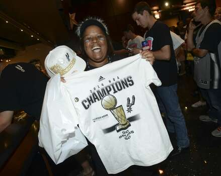 Vicki Hudson displays her Spurs championship tee shirt, which she bought in the AT&T Center minutes after the San Antonio Spurs defeated the Miami Heat in the NBA Finals on Sunday, June 15, 2014. Photo: San Antonio Express-News