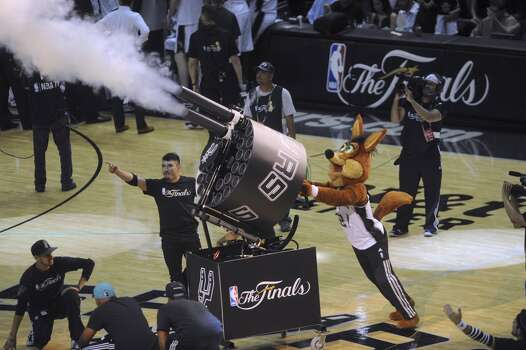 The Spurs Coyote shoots a multishot tee shirt cannon during a timeout of the San Antonio Spurs and Miami Heat game 5 in the NBA Finals in the AT&T Center on Sunday, June 15, 2014. Photo: San Antonio Express-News