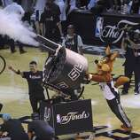 The Spurs Coyote shoots a multishot tee shirt cannon during a timeout of the San Antonio Spurs and Miami Heat game 5 in the NBA Finals in the AT&T Center on Sunday, June 15, 2014.