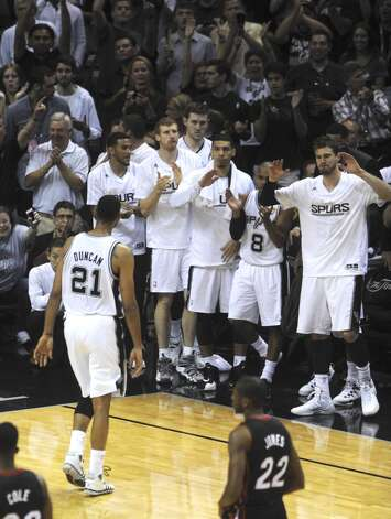Tim Duncan, the San Antonio Spurs elder statesman, is greeted by teammates after being relieved in the last minutes of the team's victory over the Miami Heat in the NBA Finals in the AT&T Center on Sunday, June 15, 2014. Photo: San Antonio Express-News