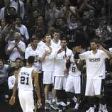 Tim Duncan, the San Antonio Spurs elder statesman, is greeted by teammates after being relieved in the last minutes of the team's victory over the Miami Heat in the NBA Finals in the AT&T Center on Sunday, June 15, 2014.