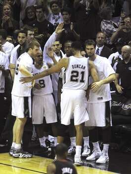 Tim Duncan, the Spurs' elder statesman, is greeted by teammates after being relieved in the final minutes of the team's victory over the Miami Heat in the NBA Finals in the AT&T Center on Sunday, June 15, 2014. Duncan earned his fifth NBA championship ring. Photo: San Antonio Express-News