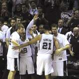 Tim Duncan, the Spurs' elder statesman, is greeted by teammates after being relieved in the final minutes of the team's victory over the Miami Heat in the NBA Finals in the AT&T Center on Sunday, June 15, 2014. Duncan earned his fifth NBA championship ring.