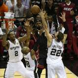 Miami Heat's LeBron James is surrounded by the Spurs defense during the first quarter of game five of the NBA Finals at the AT&T Center, Sunday, June 15, 2014.