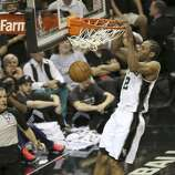 San Antonio Spurs' Kawhi Leonard slams the ball home as Miami Heat's LeBron James watches during the first quarter of game five of the NBA Finals at the AT&T Center, Sunday, June 15, 2014.