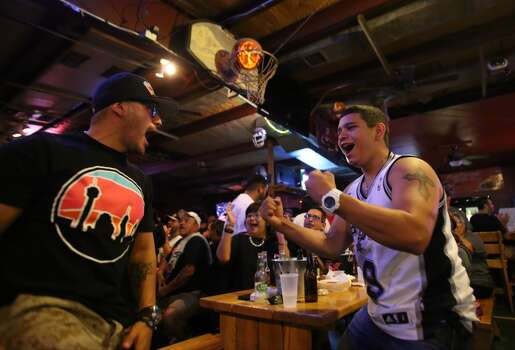 Ruben Hernandez, left, and Luke Villalpando celebrate after a point by the Spurs during Game 5 of the NBA Finals on Sunday, June 15, 2014, at Fatso's Sports Garden in San Antonio. General manager Jim Woods estimated about 500 customers were present to watch the game. Photo: San Antonio Express-News