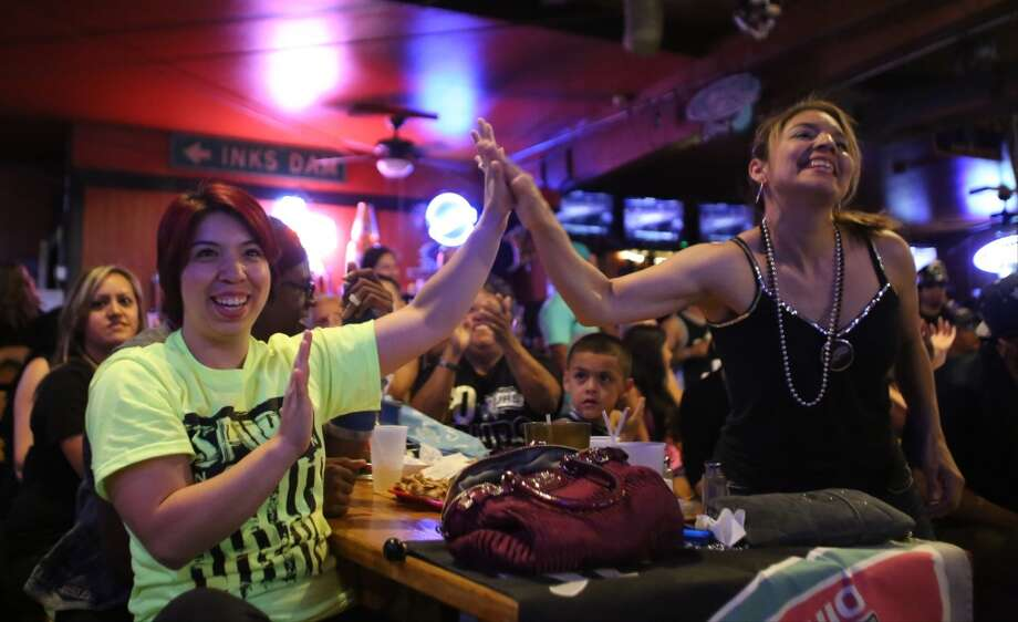 Emma King, left, high-fives her sister, Charity Rivera, on Sunday, June 15, 2014, at Fatso's Sports Garden in San Antonio. Rivera said the two have been coming to Fatso's to watch NBA championship games since 1999. Photo: San Antonio Express-News