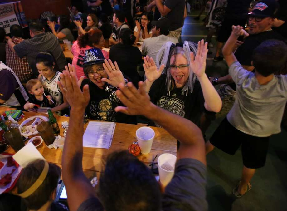 Gloria Padilla, center left, and Emily New, center right, high-five New's husband, Robert Mercado, bottom, after a point by the Spurs during Game 5 of the NBA Finals on Sunday, June 15, 2014, at Fatso's Sports Garden in San Antonio. General manager Jim Woods estimated about 500 customers were present to watch the game. Photo: San Antonio Express-News