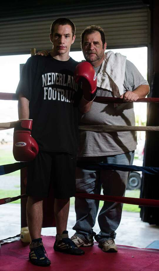 Cody Richard poses for a picture with his father C.L. in the ring Tuesday evening. Cody decided when he was eight that he wanted to take up boxing. His father has been backing and training him ever since.