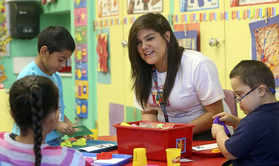Michaela Valdez (en el medio) es estudiante de South San. Aquí ella usa letras del alfabeto con estudiantes  la de la escuela Kindred Elementary. Photo: Photos By Tom Reel / San Antonio Express-News / San Antonio Express-News