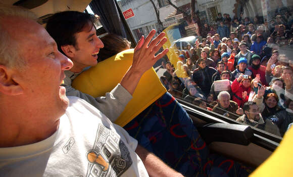 Gregg Popovich, left, and Manu Ginobili wave to a crowd from their bus as he entered Bahia Blanca, Arg., his hometown, Monday, July 4, 2005. Photo: BOB OWEN, BOB OWEN/San Antonio Express-News / SAN ANTONIO EXPRESS-NEWS