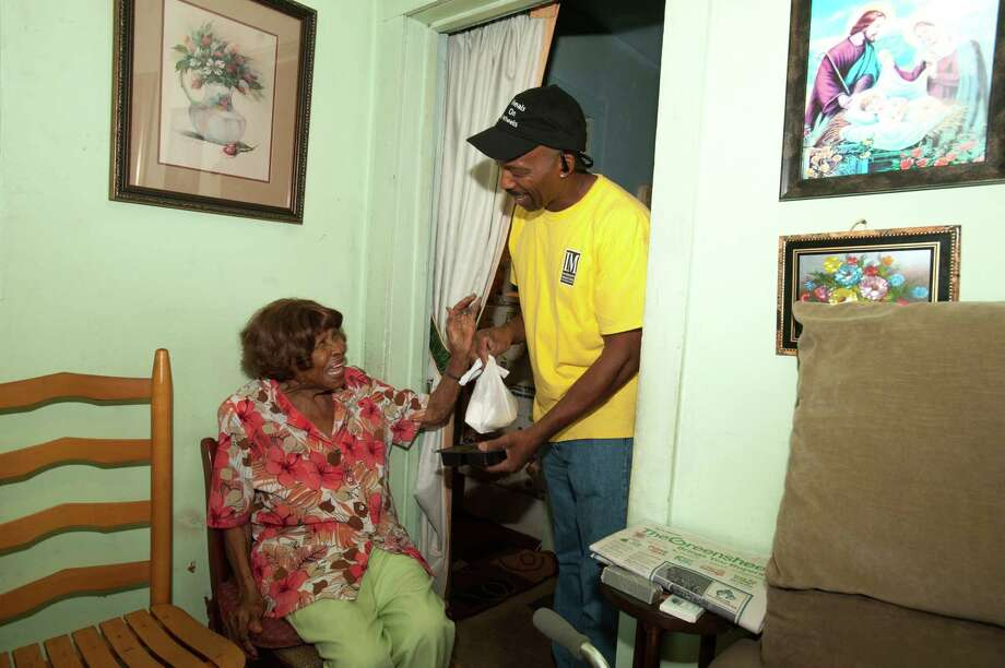 Meals on Wheels customer Lurline Gardner collects an order from driver Clyde Samples. / Alexander Rogers