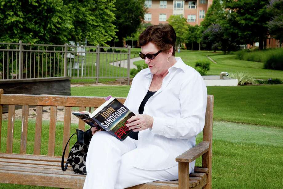 Eagle's Trace resident Fran Gleeson enjoys reading by the lake during the summer. Photo: Jeremy Carter Photo