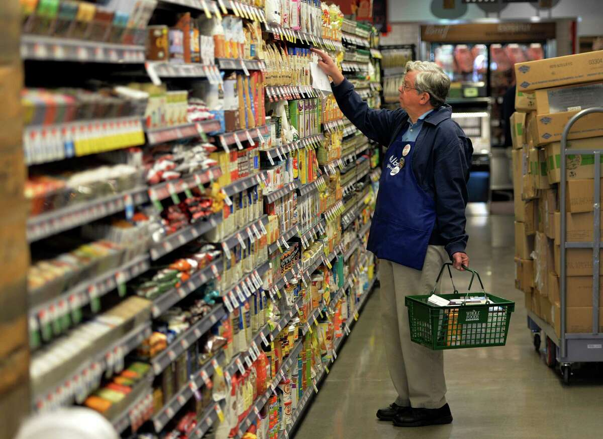 Cashier James Chambers gets acquainted with the products Monday morning June 16, 2014, as Whole Foods gets ready for its grand opening on Wednesday at Colonie Center in Colonie, N.Y. (Skip Dickstein / Times Union)