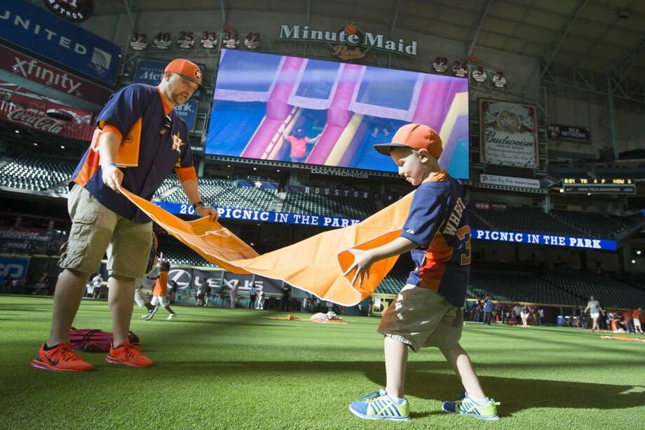 Dewayne Wheeland and his son, Riley, spread out their picnic mat. Photo: Brett Coomer, Houston Chronicle