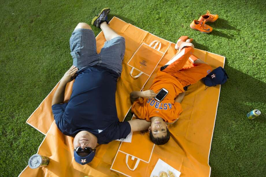 Jessie Gonzales, left, lies back in the outfield with his son, Jessie. Photo: Brett Coomer, Houston Chronicle