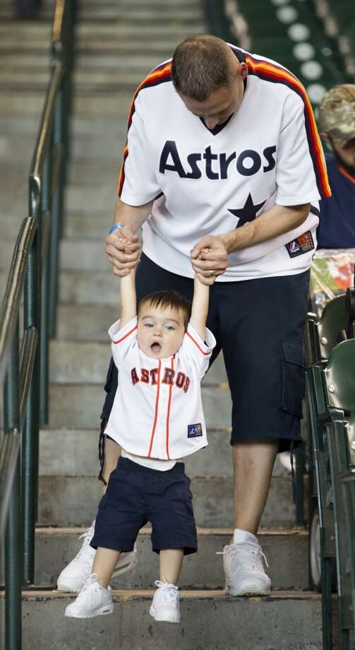 Chris Dennis helps his son, Brock, down the stairs toward the field. Photo: Brett Coomer, Houston Chronicle
