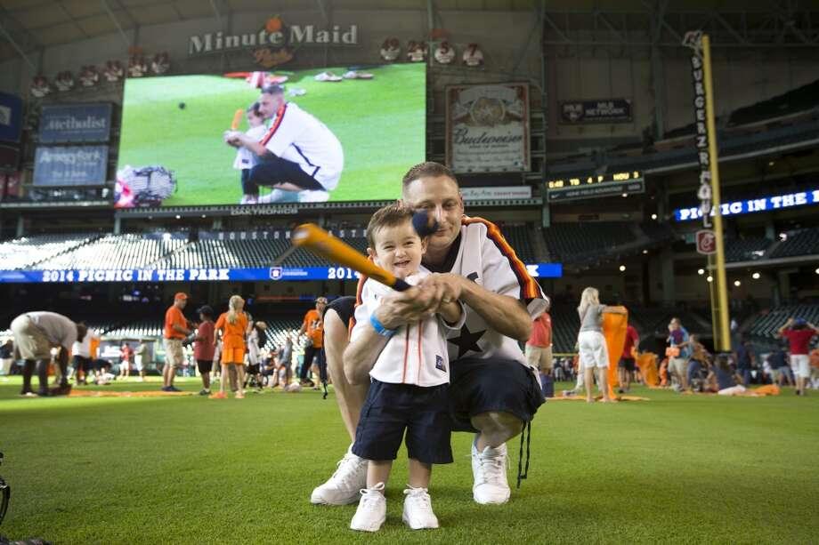 Chris Dennis helps his son, Brock, swing the bat. Photo: Brett Coomer, Houston Chronicle