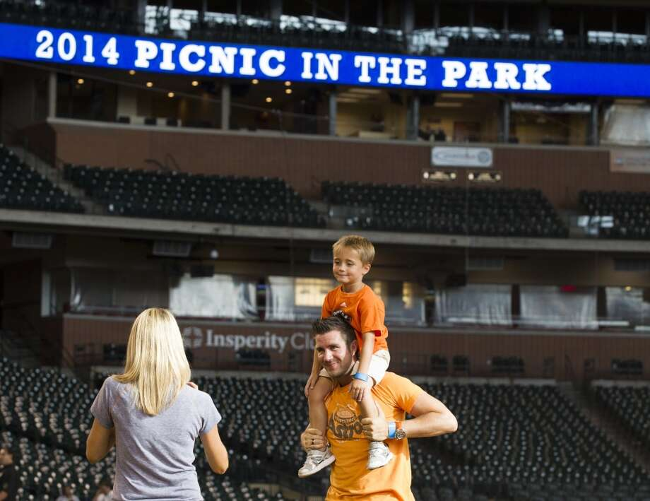 Hunter Borchers, 5, sits on his dad, Jeremy Borchers' shoulders as Liz Borchers takes photos of them. Photo: Brett Coomer, Houston Chronicle