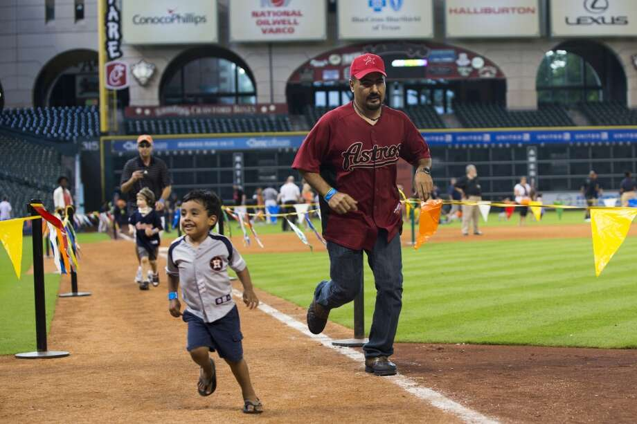 Kids and parents run the bases. Photo: Brett Coomer, Houston Chronicle