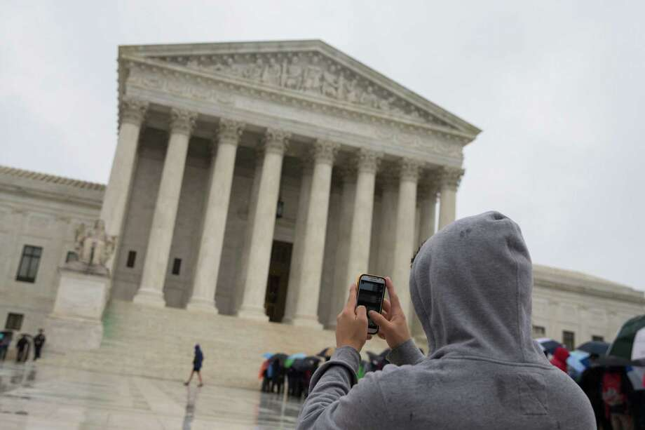 "FILE - This April 29, 2014 file photo shows a visitor to the Supreme Court uses his cellphone to take a photo of the court in Washington. A divided Supreme Court sided with gun control groups and the Obama administration Monday, ruling that the federal ban on ""straw"" purchases of guns can be enforced even if the ultimate buyer is legally allowed to own a gun. The justices ruled 5-4 that the law applied to a Virginia man who bought a gun with the intention of transferring it to a relative in Pennsylvania who was not prohibited from owning firearms. Photo: Evan Vucci, AP / AP"
