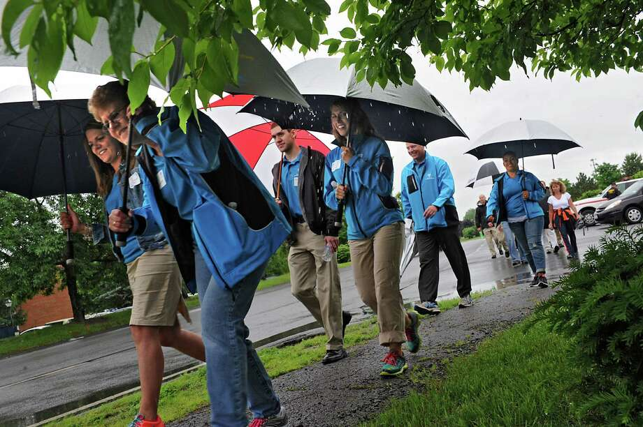 Participants from area businesses braved the rain as they took part in a lunchtime employee wellness walk from the Clifton Park-Halfmoon Emergency Corps to the Cracker Barrel on Crossing Boulevard Friday, June 13, 2014, in Clifton Park, N.Y. The mile walk was hosted by the Saratoga County Chamber's Twin Bridges Council. (Lori Van Buren / Times Union) Photo: Lori Van Buren / 00027090A
