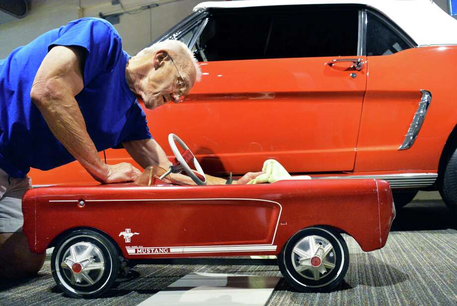 Docent volunteer, Bob Pommerer of Saratoga Springs details a Mustang peddle car next to one of the first Mustangs ever built, a 1964 1/2 pre production car, Friday, June 13, 2014, at the Saratoga Automobile Museum in Saratoga Springs, NY. This year's featured summer exhibition celebrates the 50th anniversary of the Ford Mustang.  (John Carl D'Annibale / Times Union)) Photo: John Carl D'Annibale / 00027055A